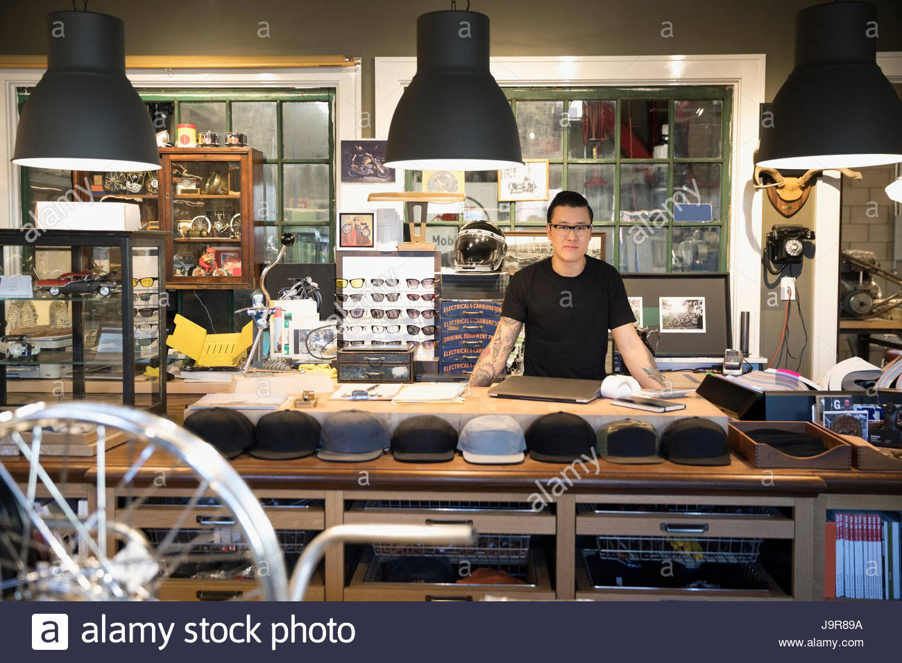 Portrait motorcycle shop owner behind counter - Stock Image