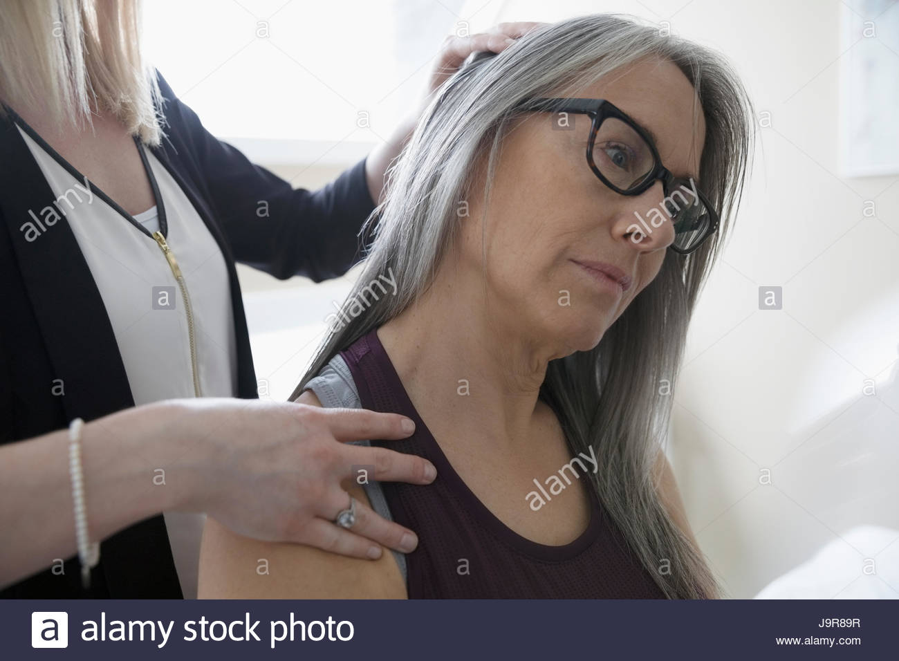 Female physiotherapist stretching neck of client in clinic examination room Stock Photo