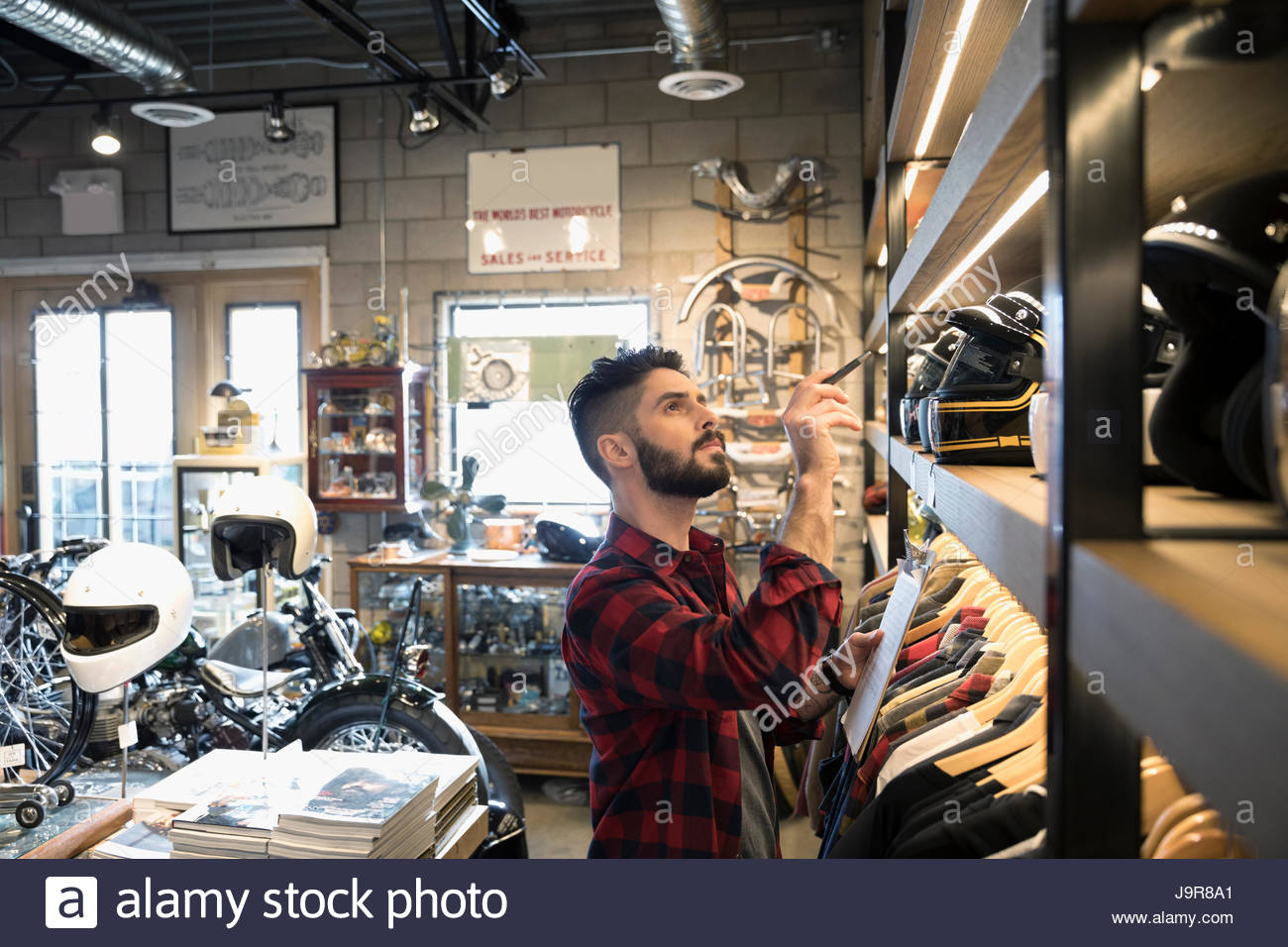 Motorcycle shop owner with clipboard checking helmet inventory - Stock Image