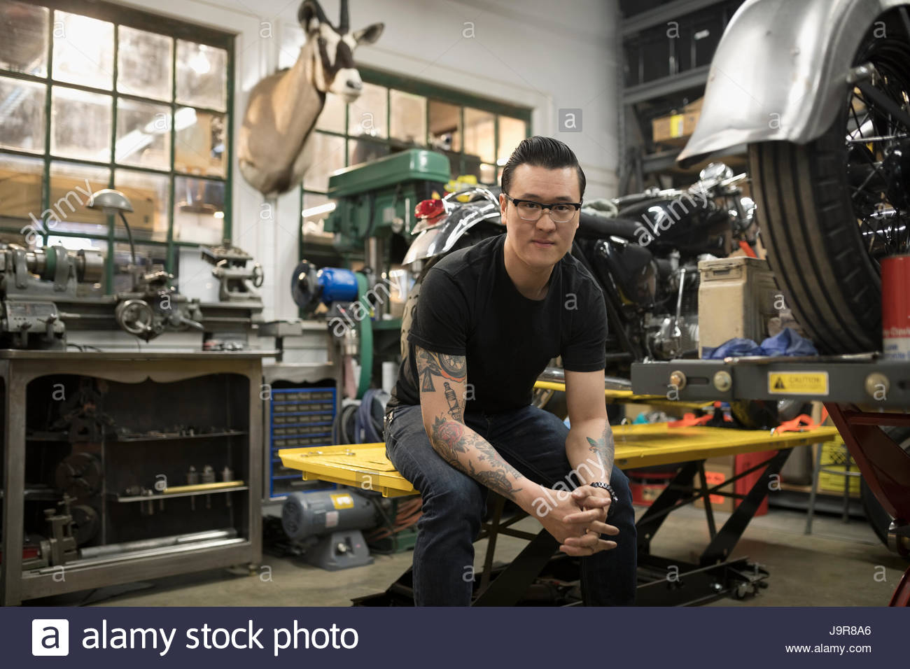 Portrait confident motorcycle mechanic in auto repair shop - Stock Image