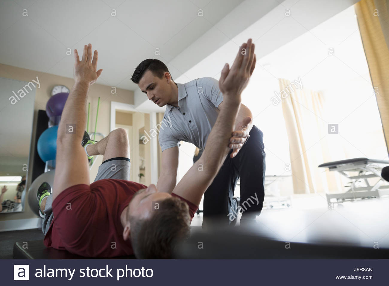 Male physiotherapist stretching client in clinic gym - Stock Image