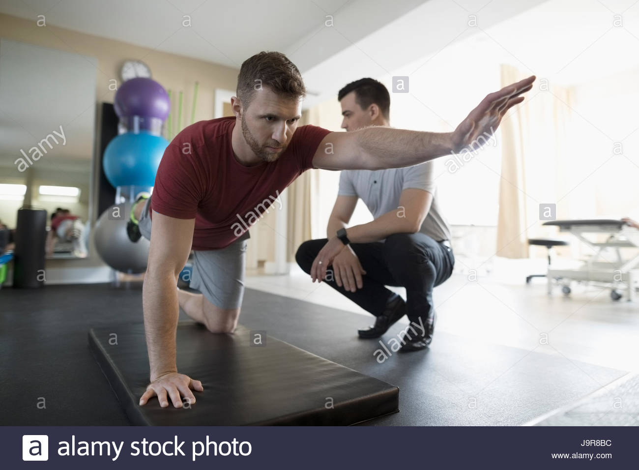 Male physiotherapist guiding client balancing in clinic gym - Stock Image