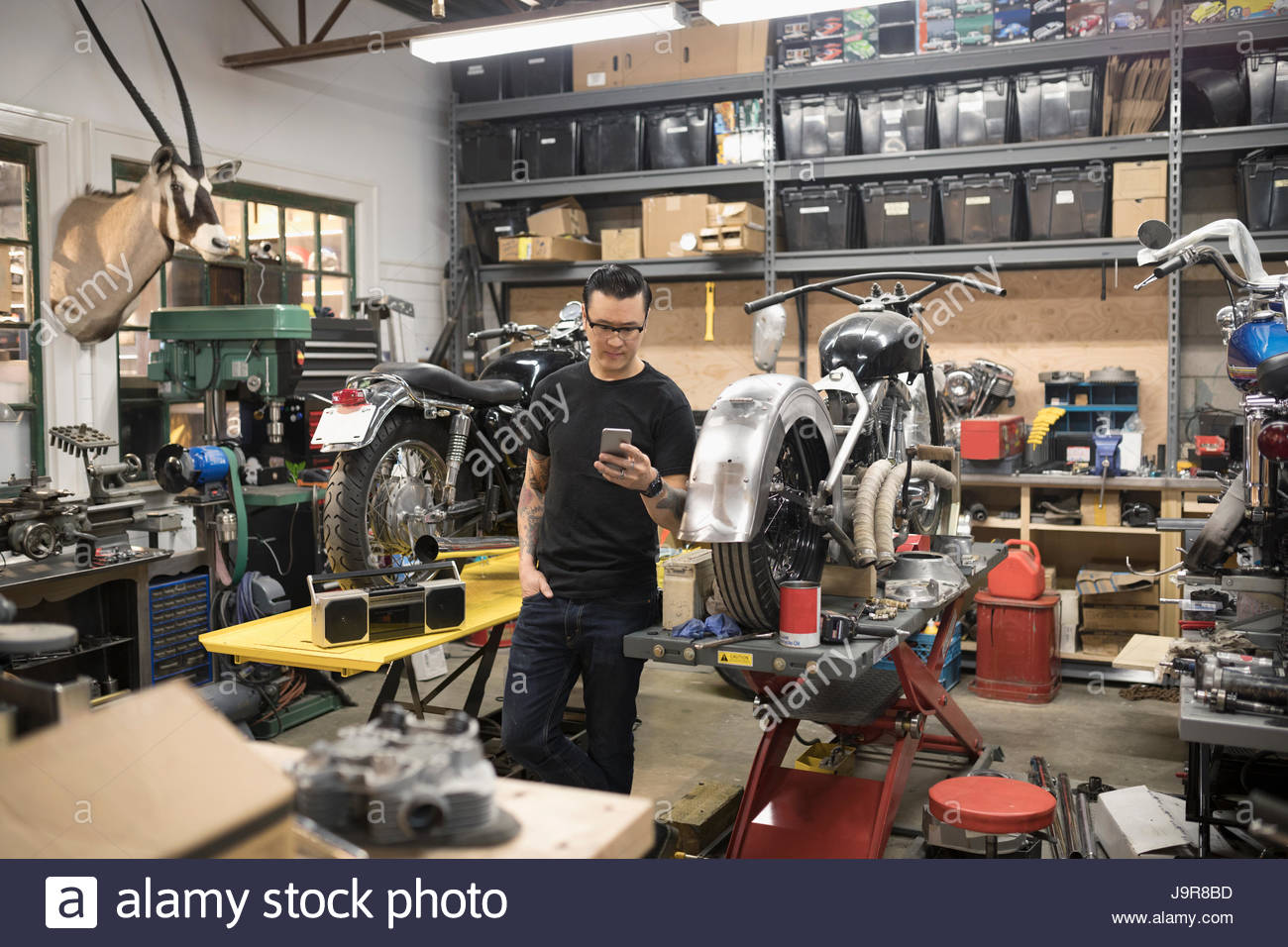Motorcycle mechanic texting with cell phone in auto repair shop - Stock Image