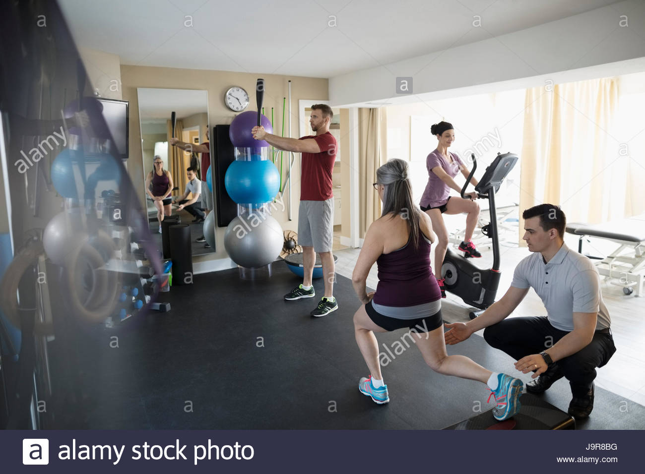 Male physiotherapist guiding clients stretching and exercising in clinic gym - Stock Image