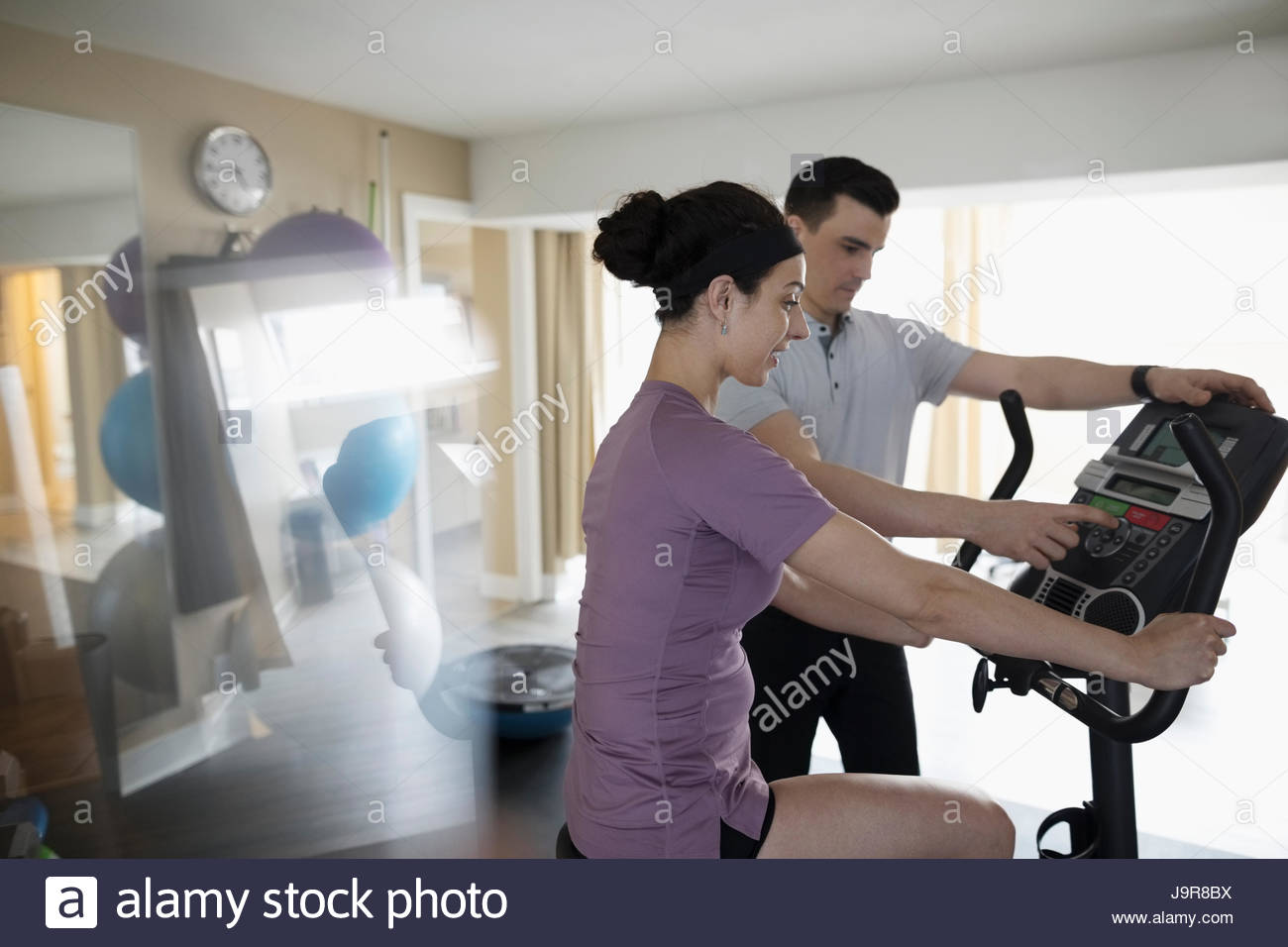 Male physiotherapist guiding female client exercising on exercise bicycle in clinic gym - Stock Image