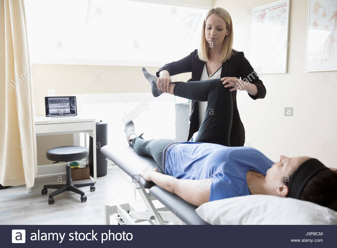 Female physiotherapist stretching woman on clinic examination room - Stock Image
