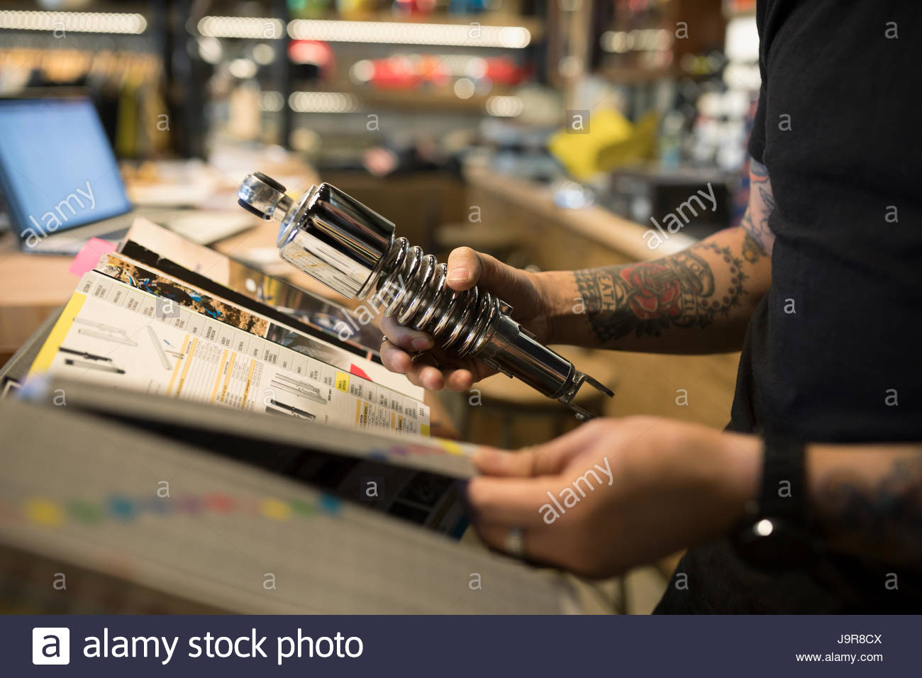 Motorcycle mechanic holding part and browsing catalog in auto repair shop - Stock Image