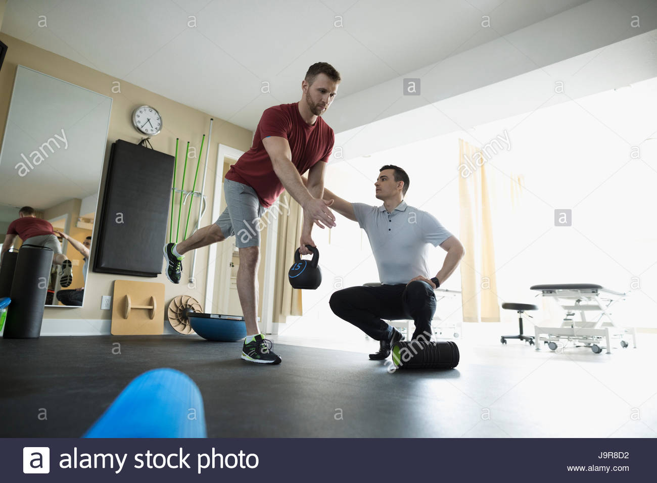 Male physiotherapist guiding client balancing with kettle bell in clinic gym - Stock Image
