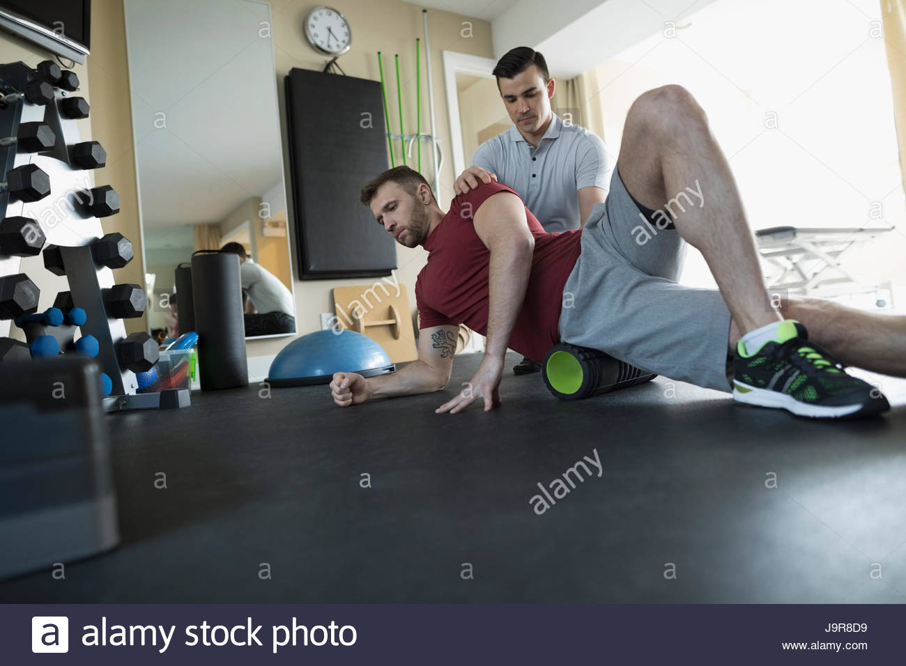 Male physiotherapist guiding client stretching in clinic gym - Stock Image