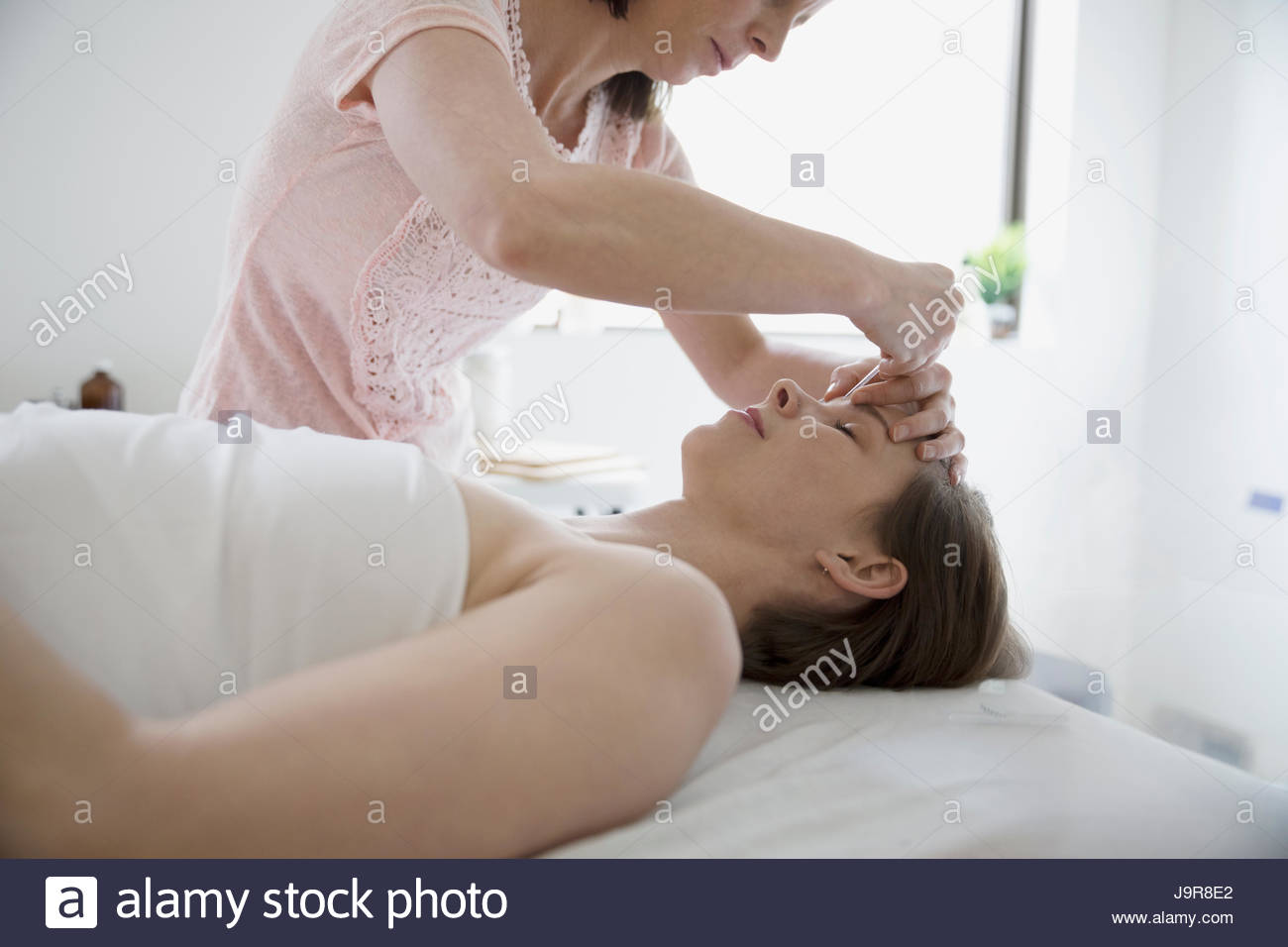 Female acupuncturist inserting needle into forehead of woman on massage table - Stock Image