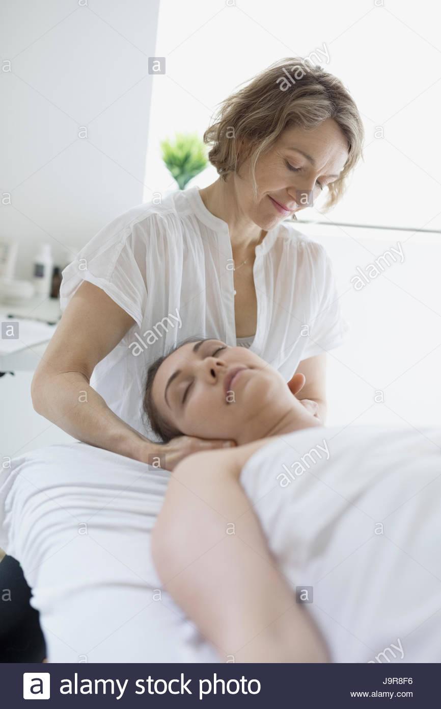 Female masseuse massaging neck of woman on spa massage table - Stock Image