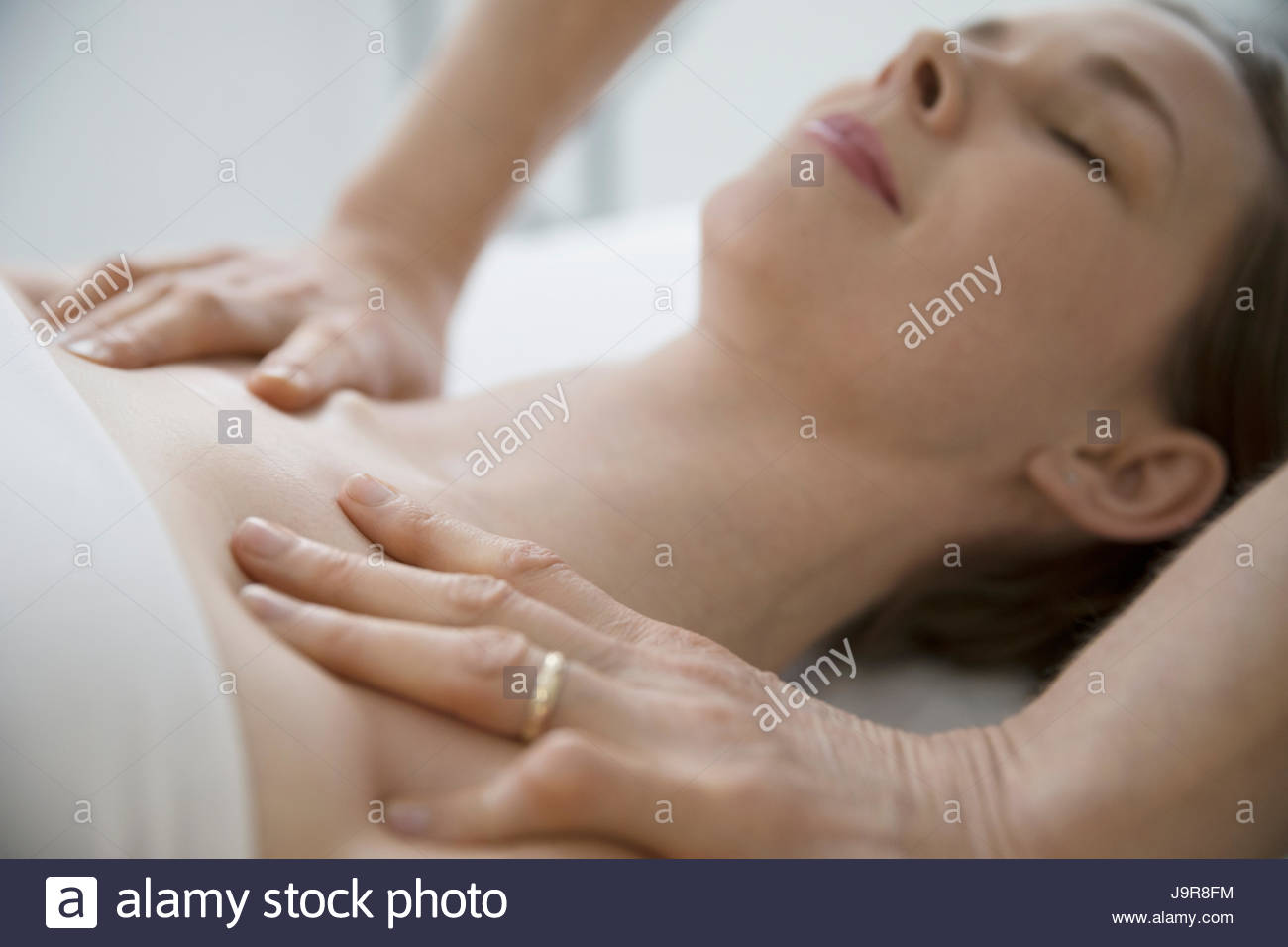 Masseuse massaging chest and shoulders of serene woman - Stock Image