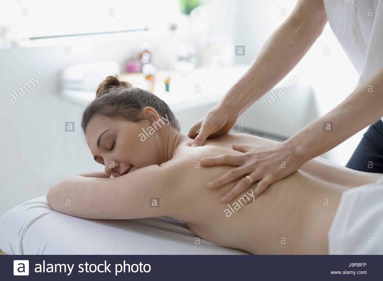 Serene woman receiving massage on spa massage table - Stock Image