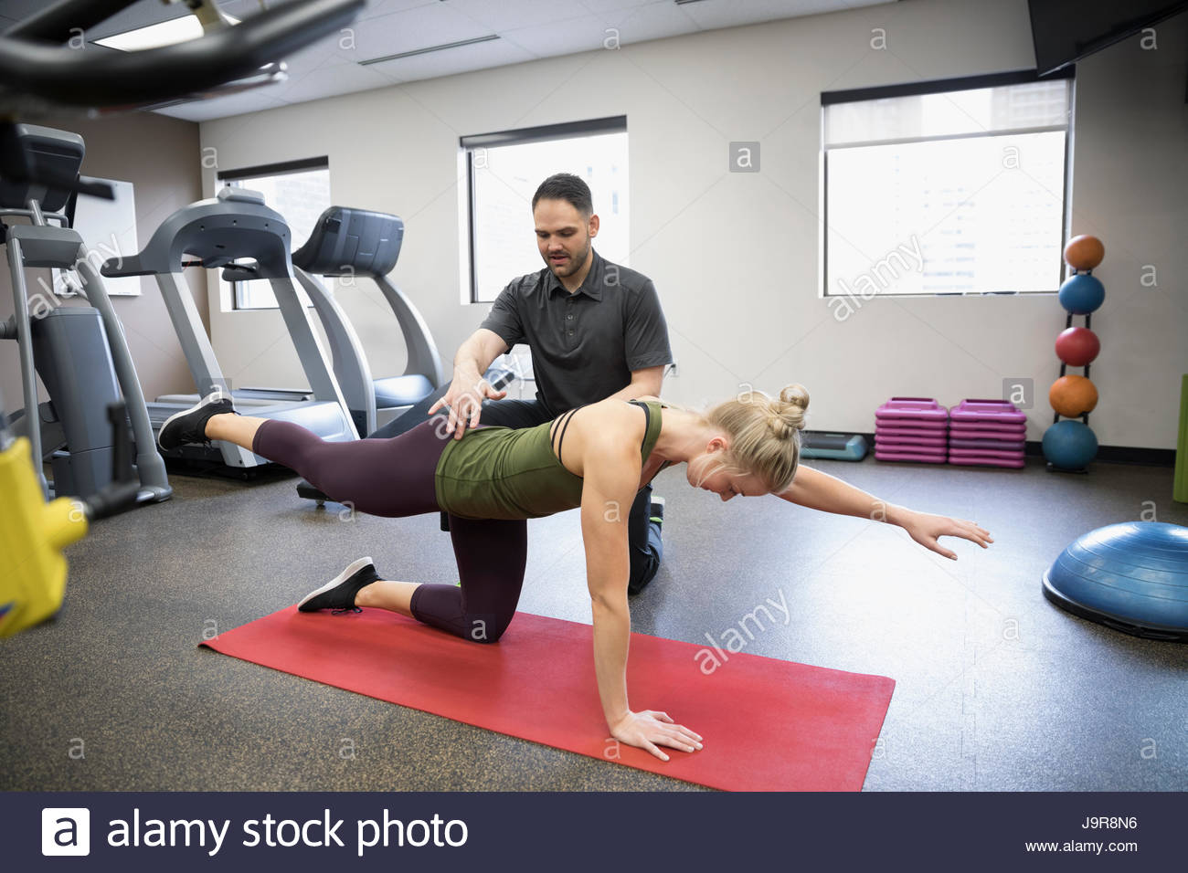 Male physiotherapist helping female client stretching in clinic gym - Stock Image