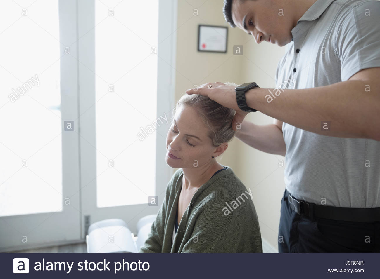 Physiotherapist stretching neck of woman in clinic examination room - Stock Image