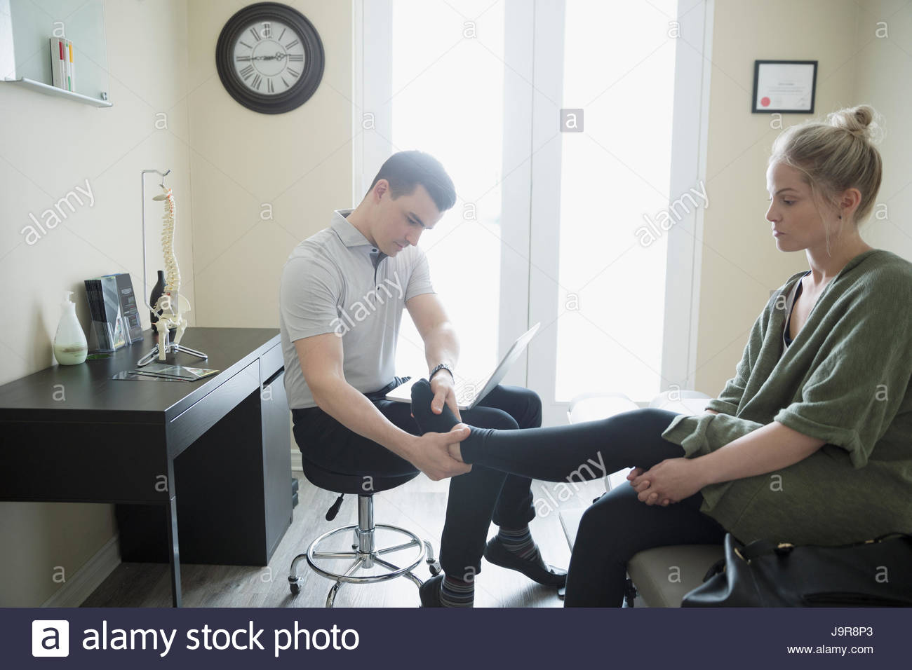 Male physiotherapist examining ankle of woman in clinic examination room - Stock Image