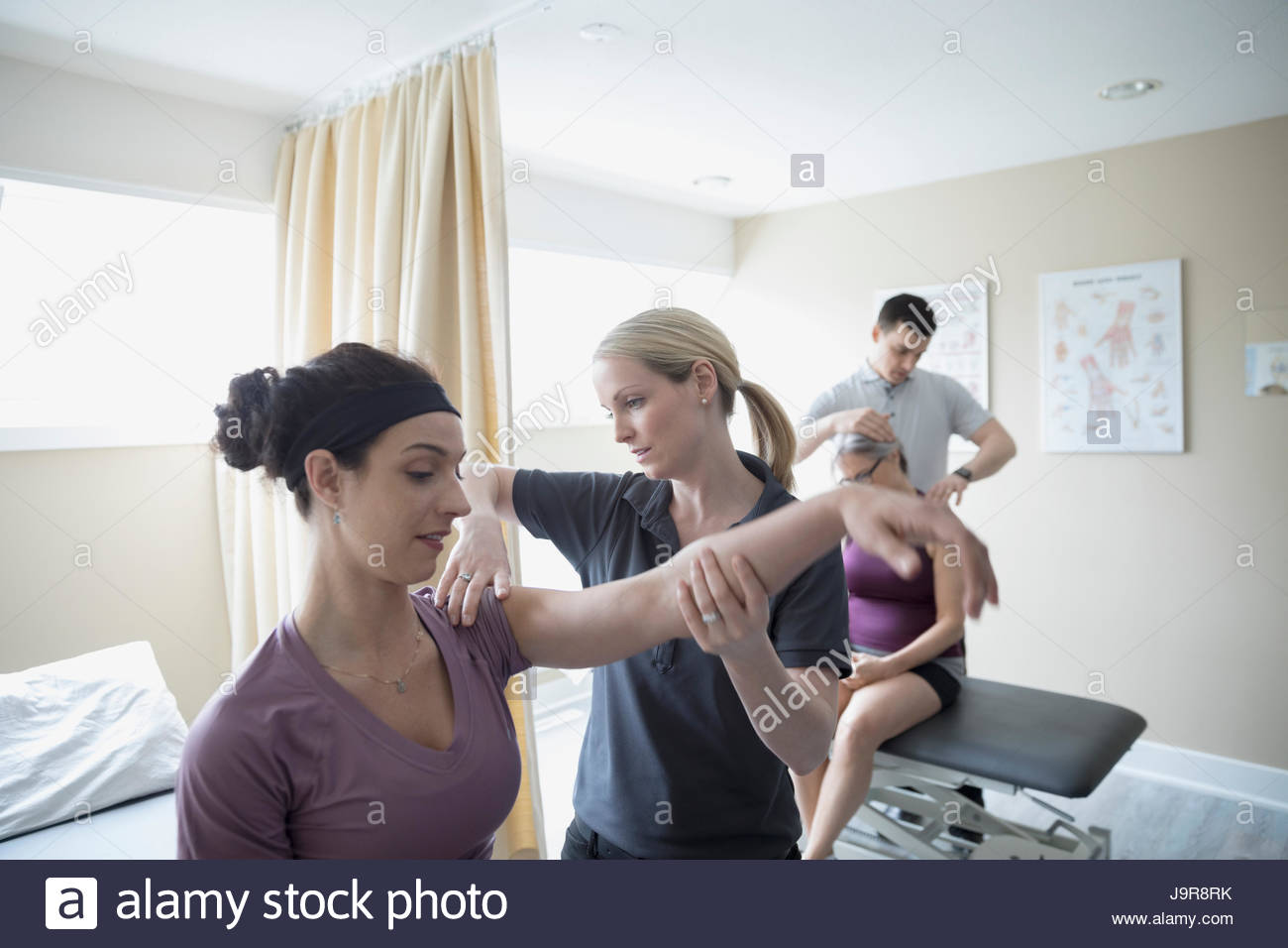 Physiotherapists examining clients in clinic - Stock Image