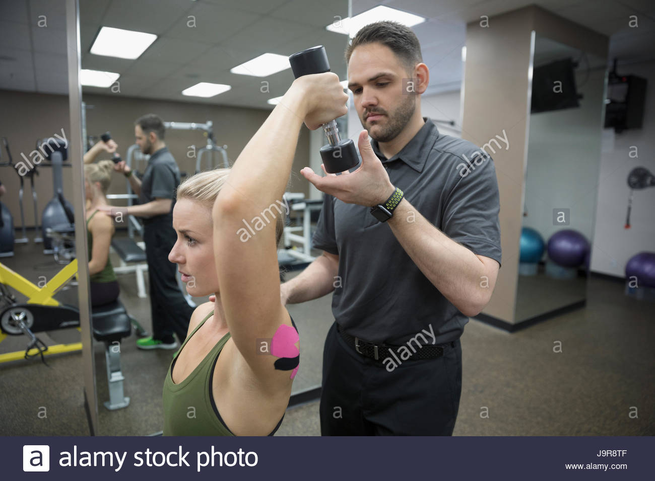 Male physiotherapist helping female client exercising with dumbbell in clinic gym Stock Photo