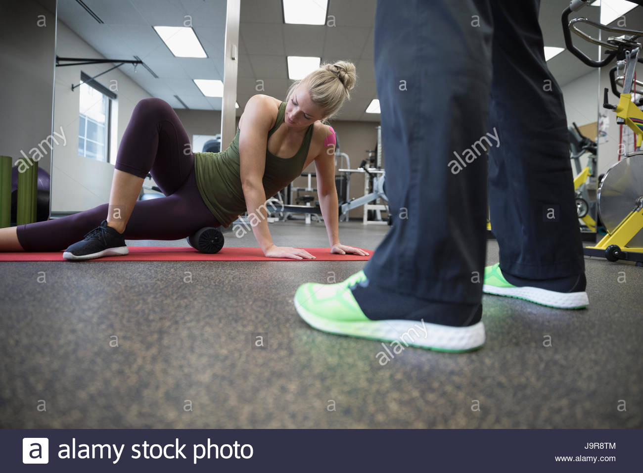 Woman stretching, exercising in gym - Stock Image