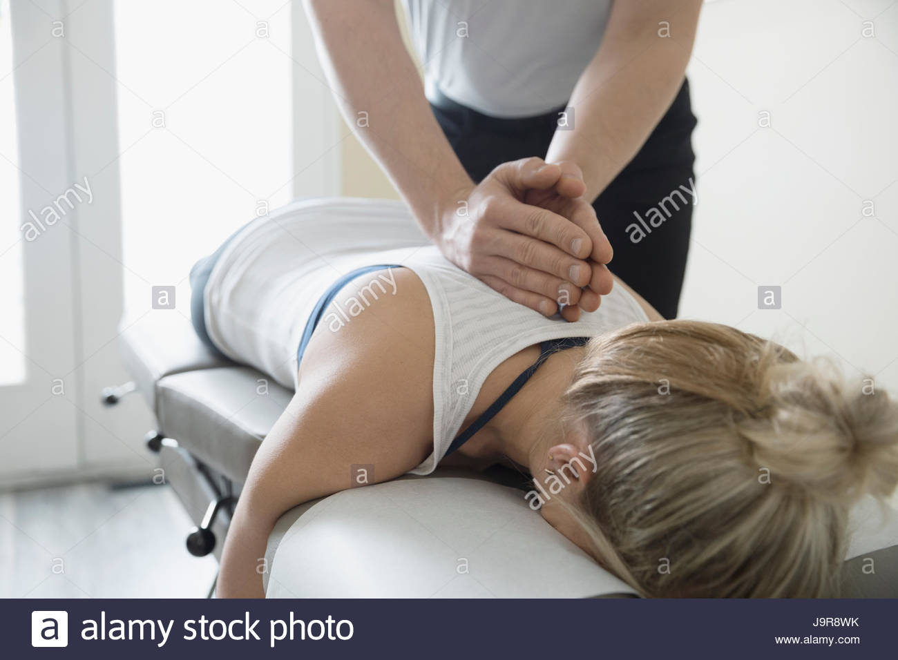 Male physiotherapist massaging back of woman on clinic examination table - Stock Image