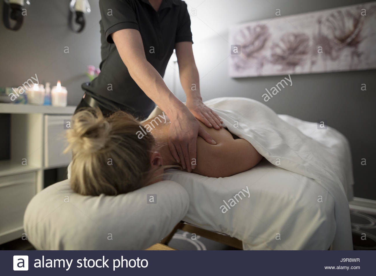 Woman receiving massage on spa massage table - Stock Image