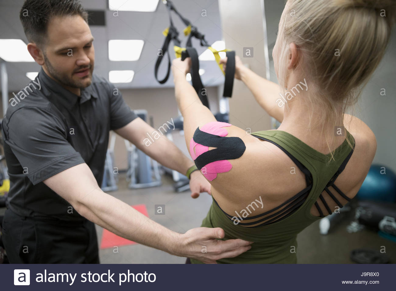 Male physiotherapist helping female client wearing elastic therapeutic tape exercising in clinic gym - Stock Image