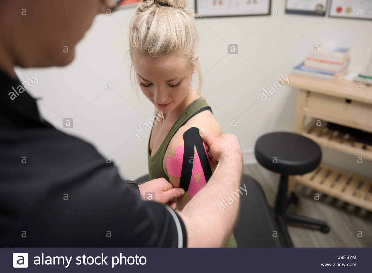 Male physiotherapist applying elastic therapeutic tape to shoulder of female client in office - Stock Image