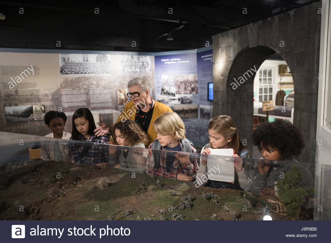 Docent and students looking at exhibit on field trip in war museum - Stock Image