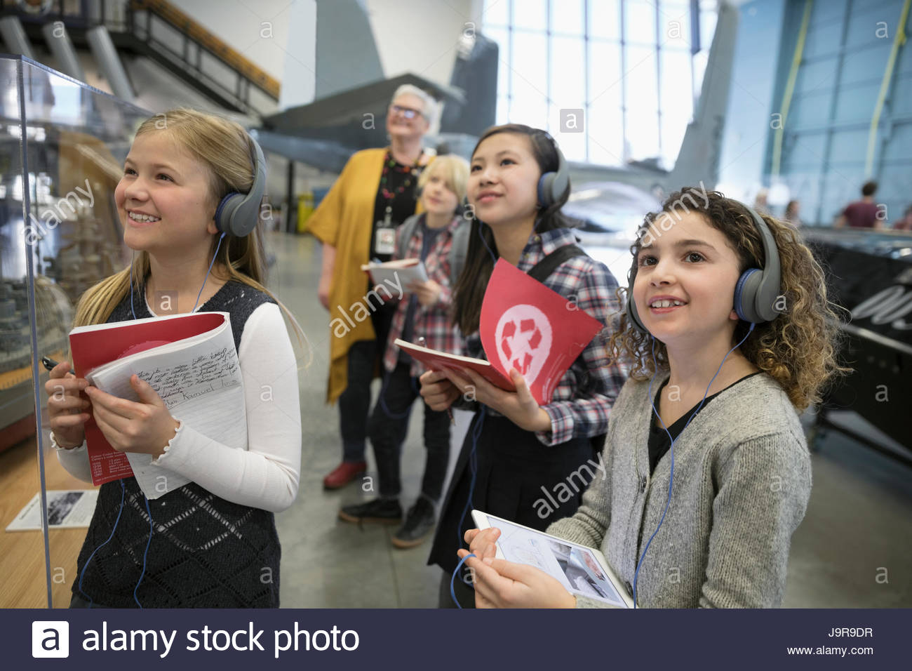 Smiling, curious students wearing headphones and taking notes at exhibit on field trip in war museum - Stock Image