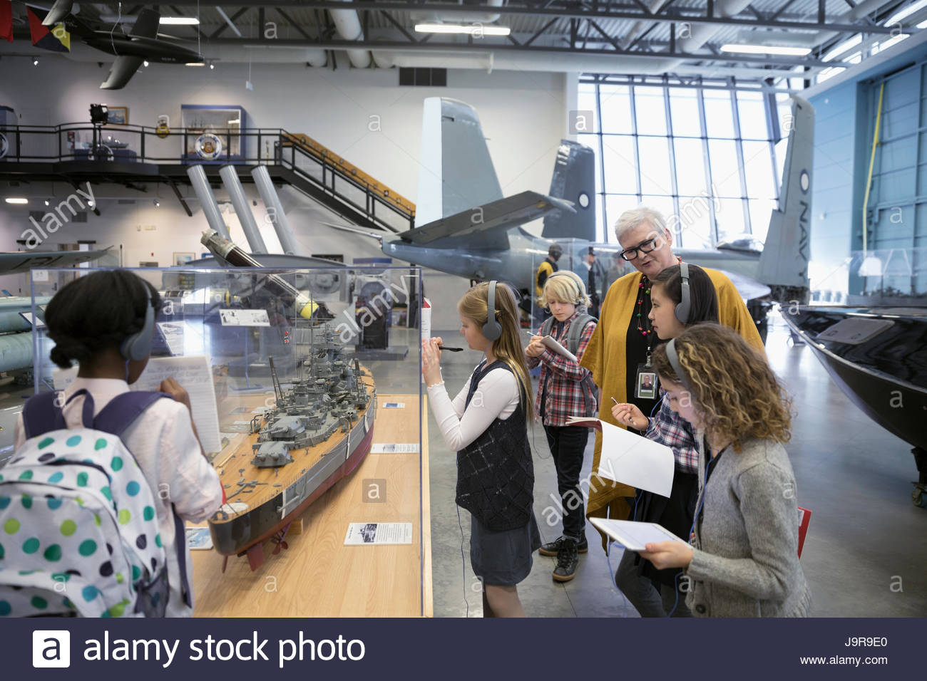 Docent helping students wearing headphones and taking notes at exhibit on field trip in war museum Stock Photo