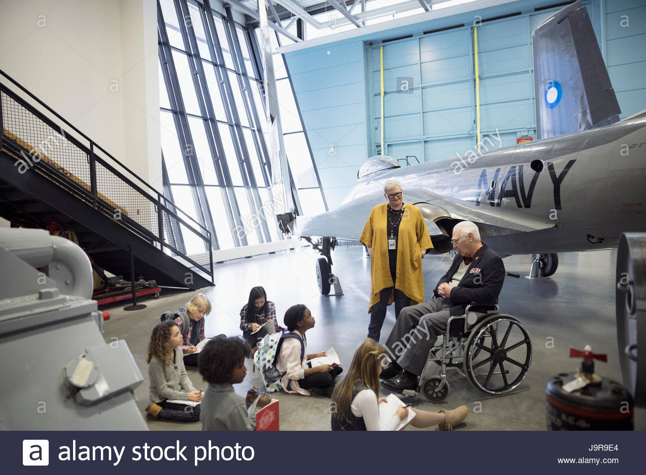 Docent and war veteran talking to students on field trip at Naval airplane in war museum hangar - Stock Image