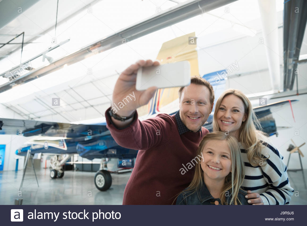 Family with smart phone taking selfie in front of airplane in war museum hangar - Stock Image