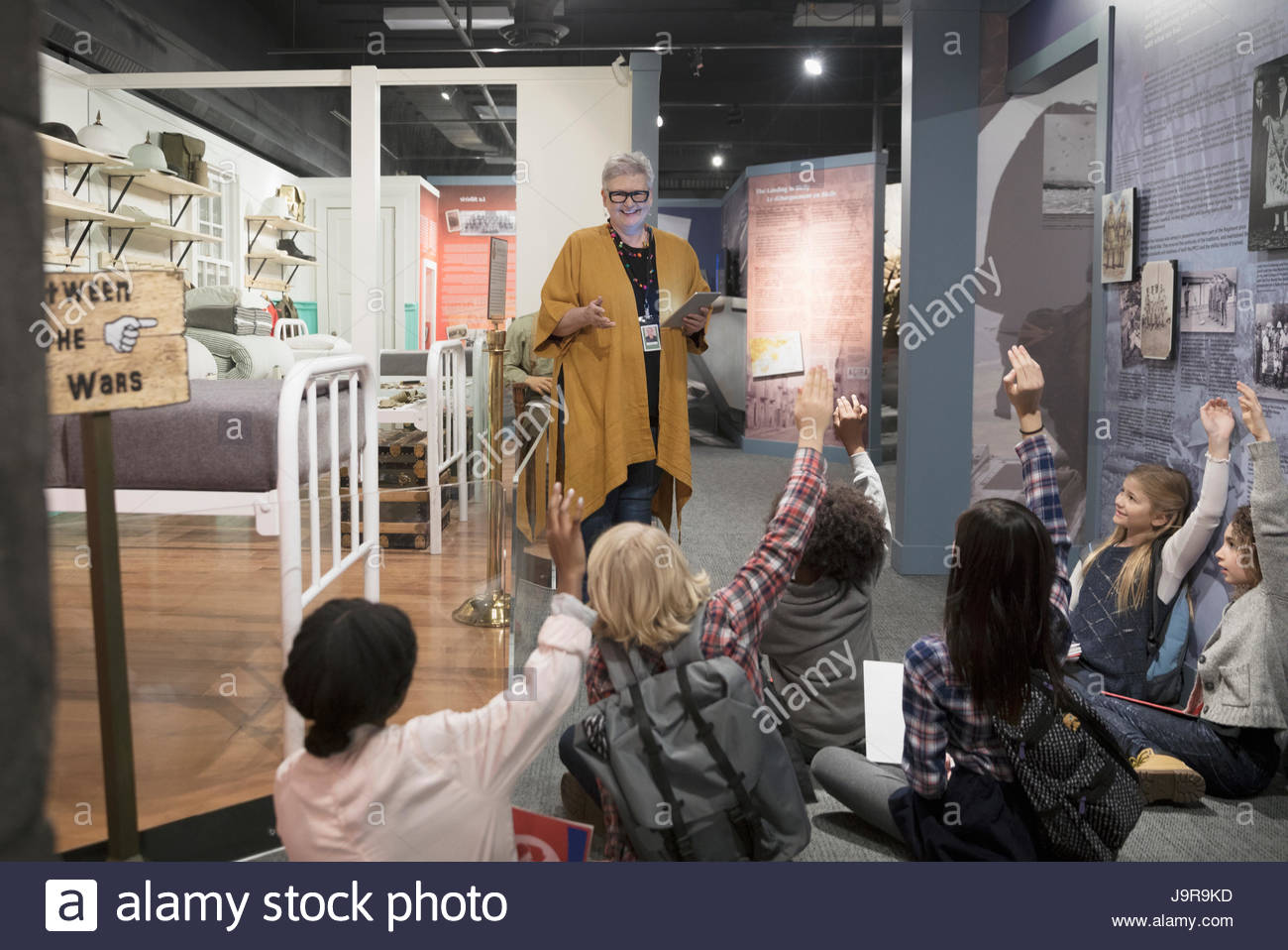 Students asking docent questions at exhibit on field trip in war museum - Stock Image