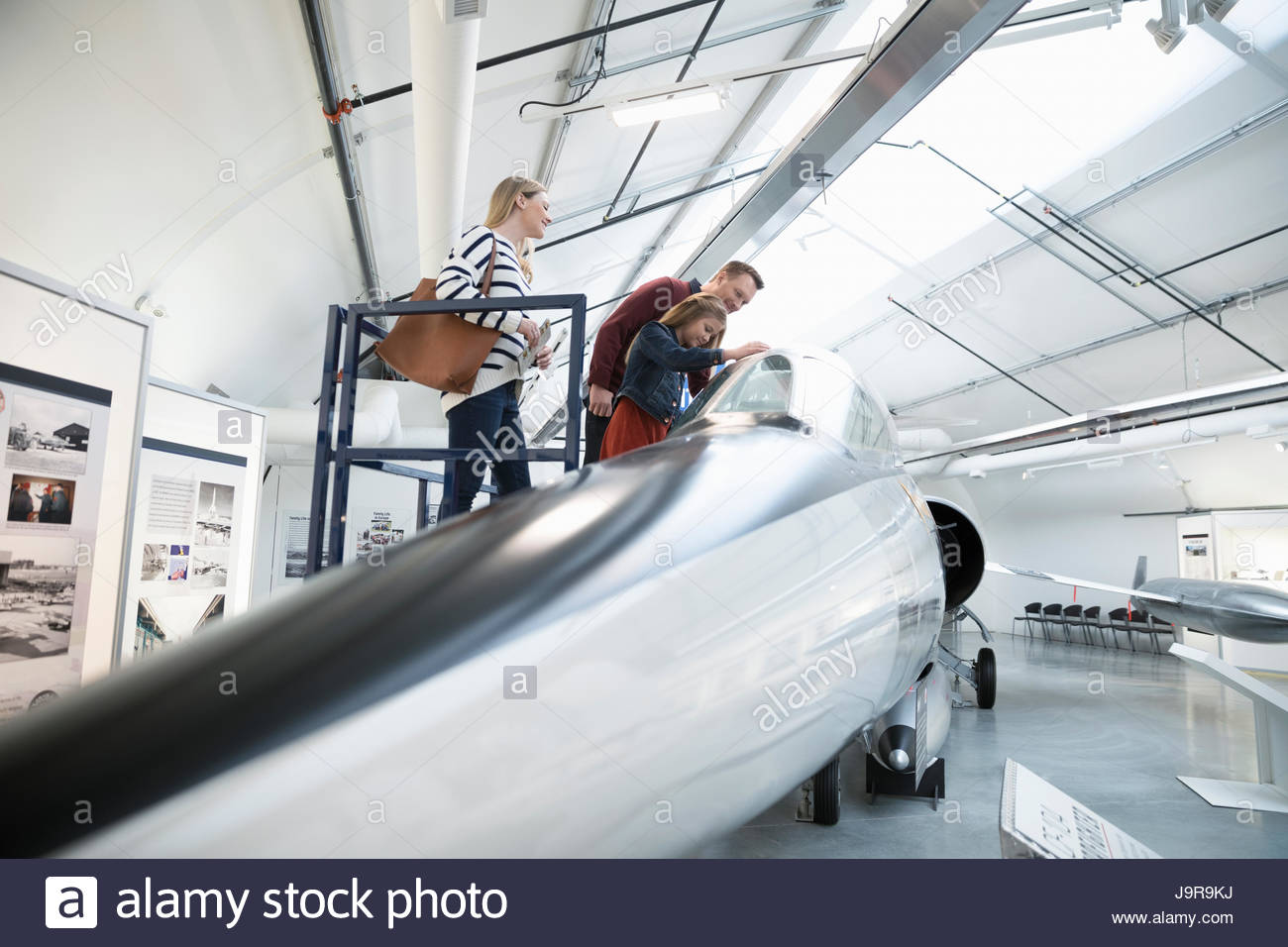 Family looking at airplane in warm museum hangar - Stock Image