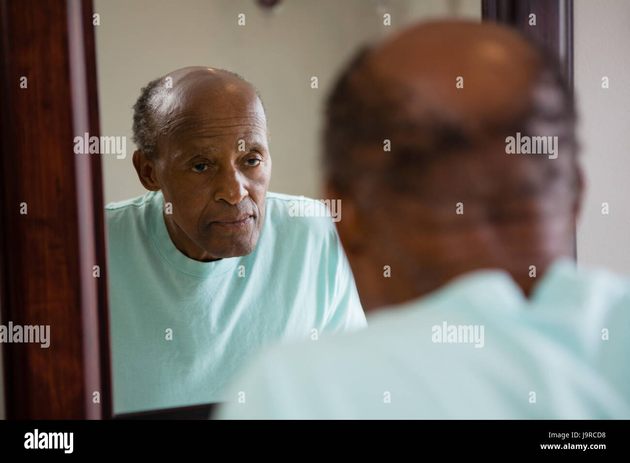 Mirror with reflection of concerned senior man in bathroom - Stock Image