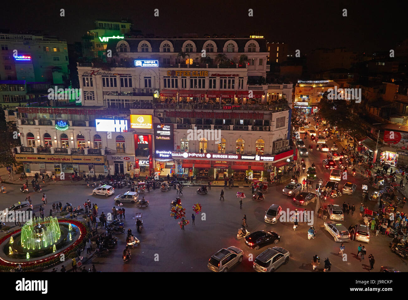 Crazy traffic at night at busy intersection by Hoan Kiem Lake and Old Quarter, Hanoi, Vietnam - Stock Image
