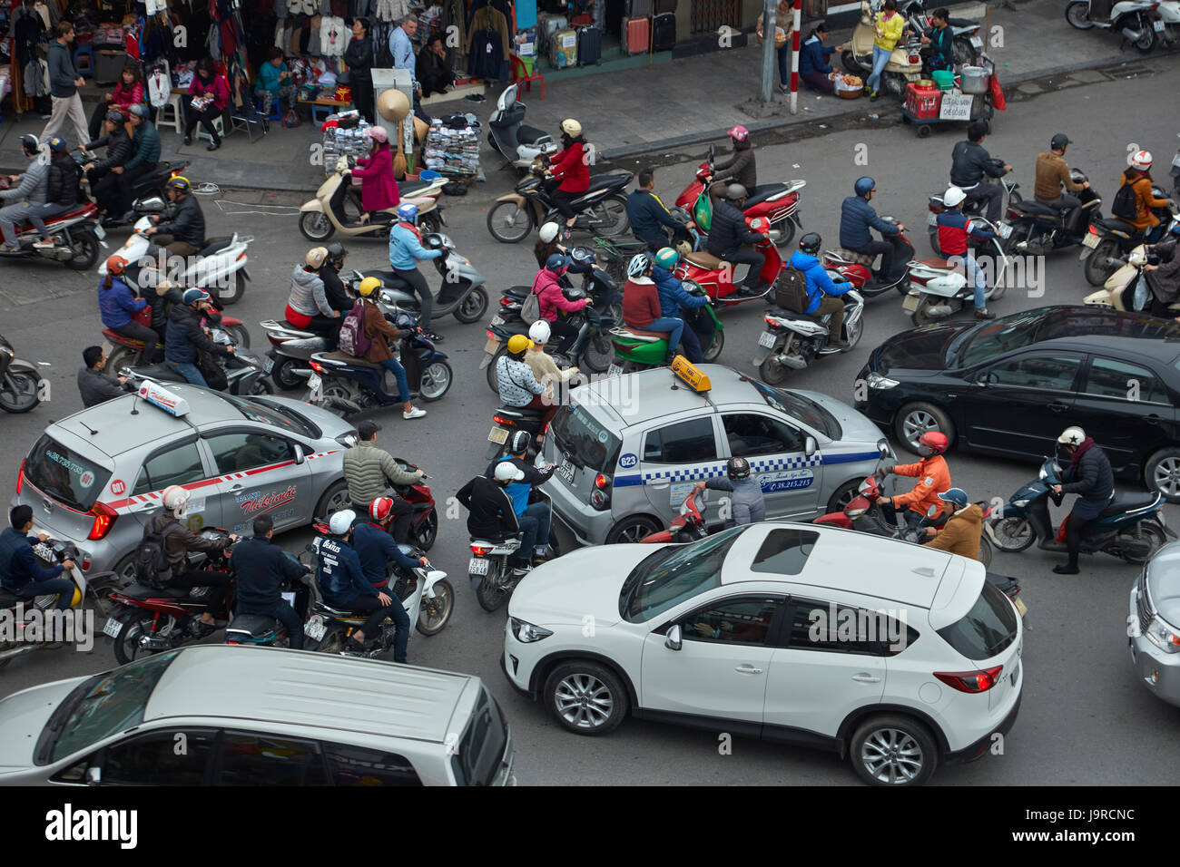 Crazy traffic at busy intersection by Hoan Kiem Lake and Old Quarter, Hanoi, Vietnam - Stock Image