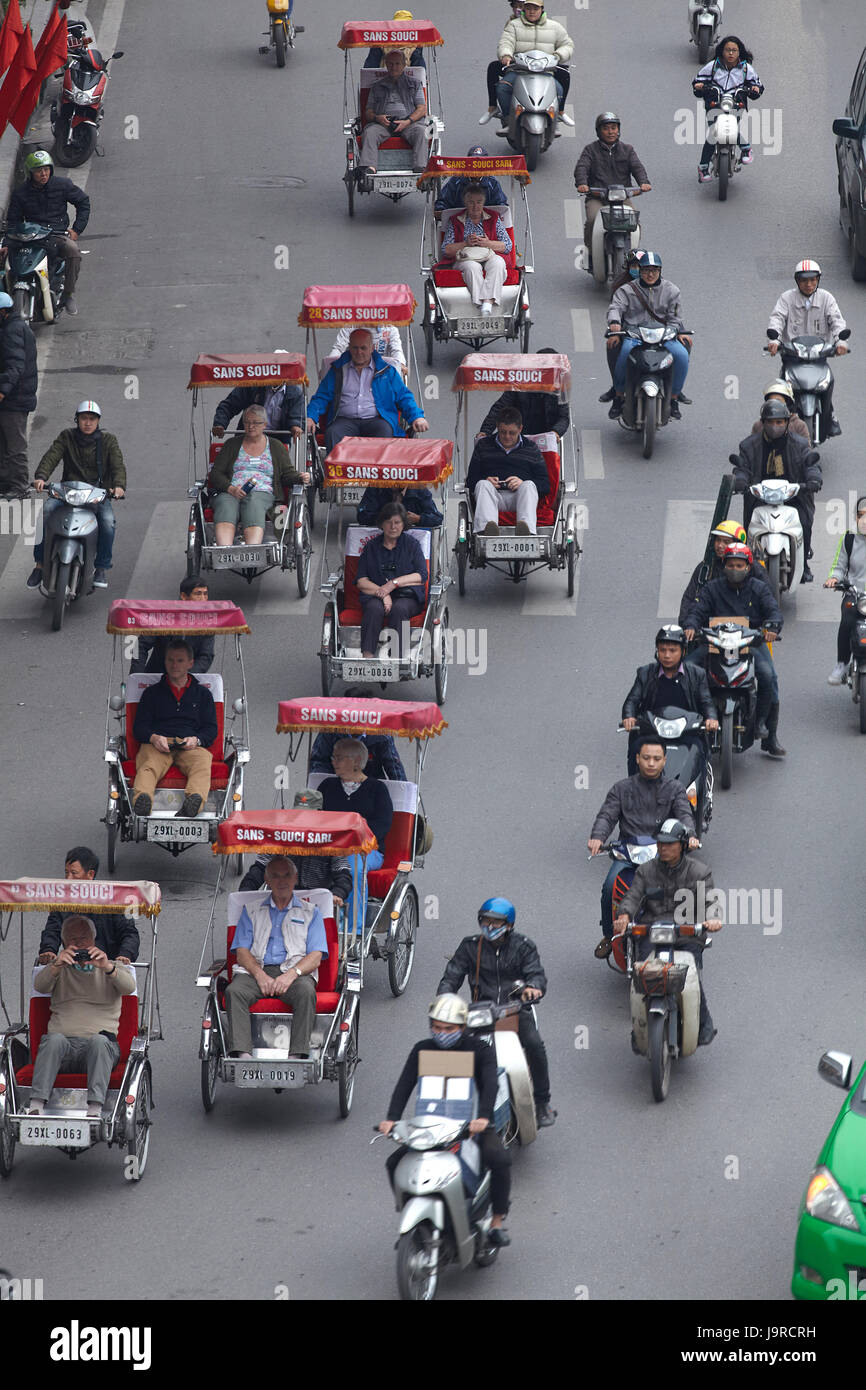 Busy street filled with rickshaws and motorcycles, Hanoi, Vietnam - Stock Image