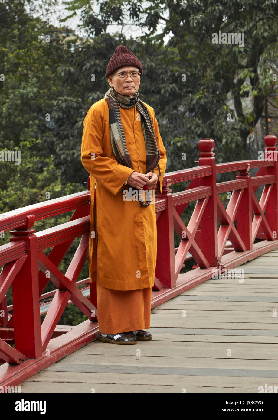 Monk on the Huc Bridge, Hoan Kiem Lake, Hanoi, Vietnam - Stock Image