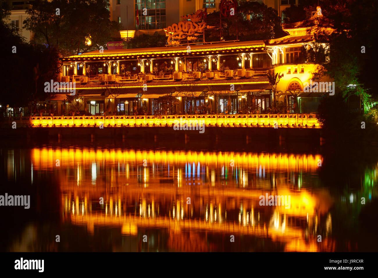 Restaurant reflected in Hoan Kiem Lake at night, Hanoi, Vietnam - Stock Image