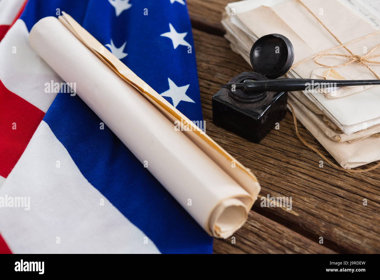 American Flag With Rolled Up Of Constitution Document On Wooden Table