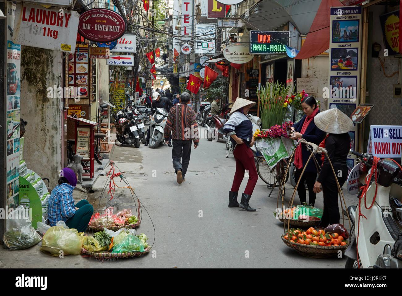 Street vendors and narrow alley, Old Quarter, Hanoi, Vietnam - Stock Image