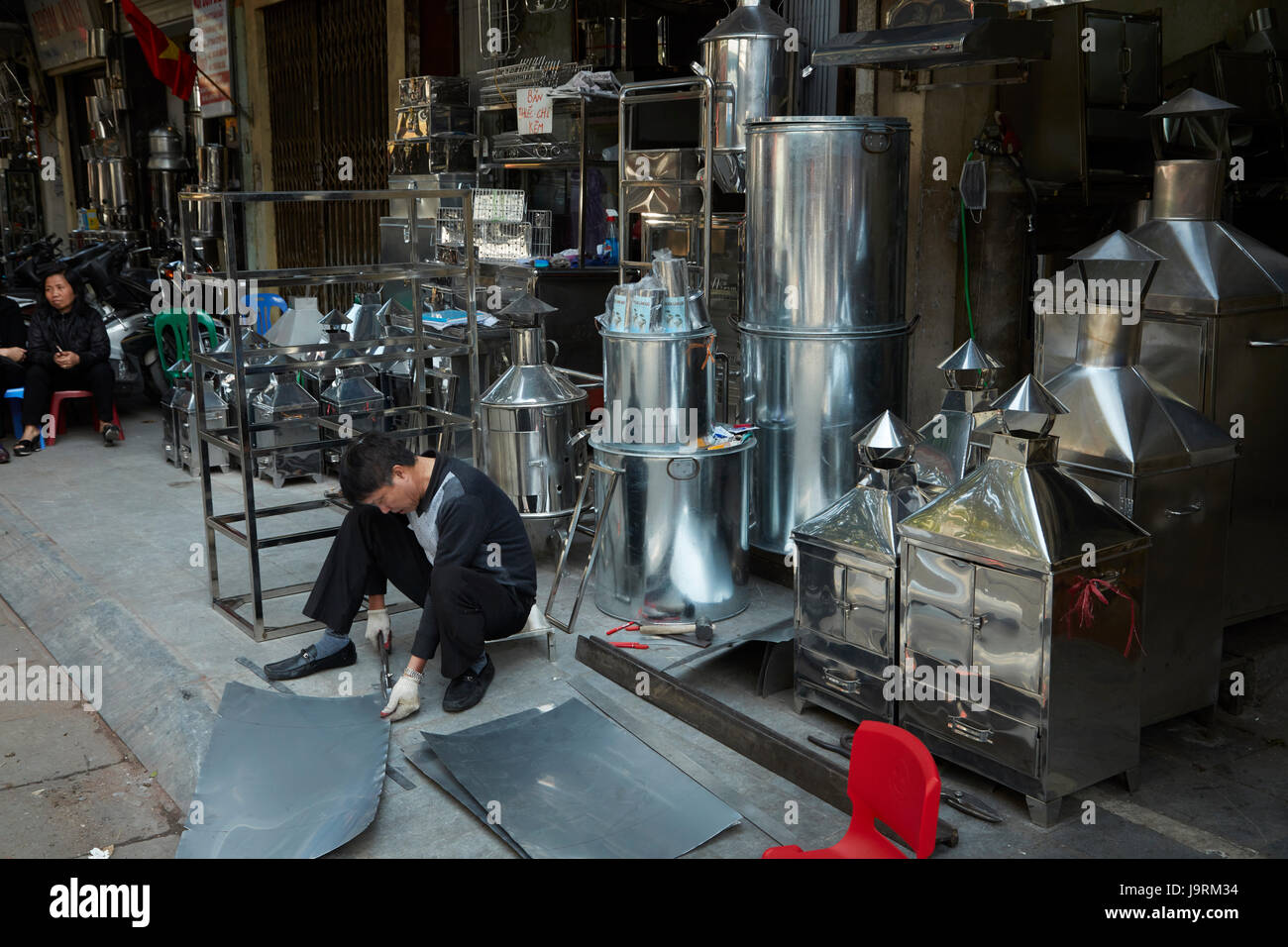 Sheet metal worker at metalwork shop, Metal Street, Old Quarter, Hanoi, Vietnam - Stock Image
