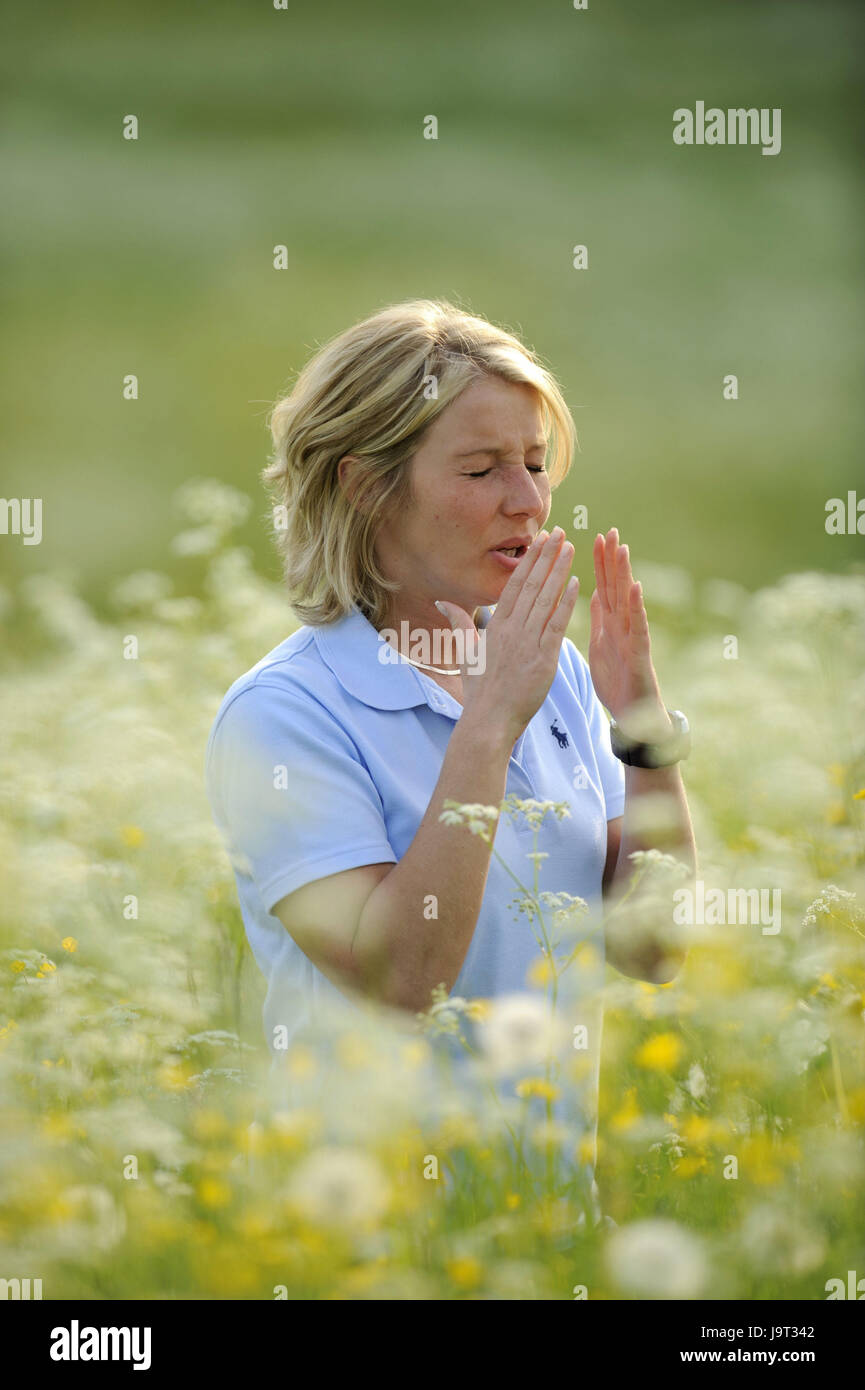 Flower meadow,woman,young,sneeze,hay fever,portrait,at the side,spring meadow,meadow,flowers,blossoms,yellow,white,blossom,icon - Stock Image