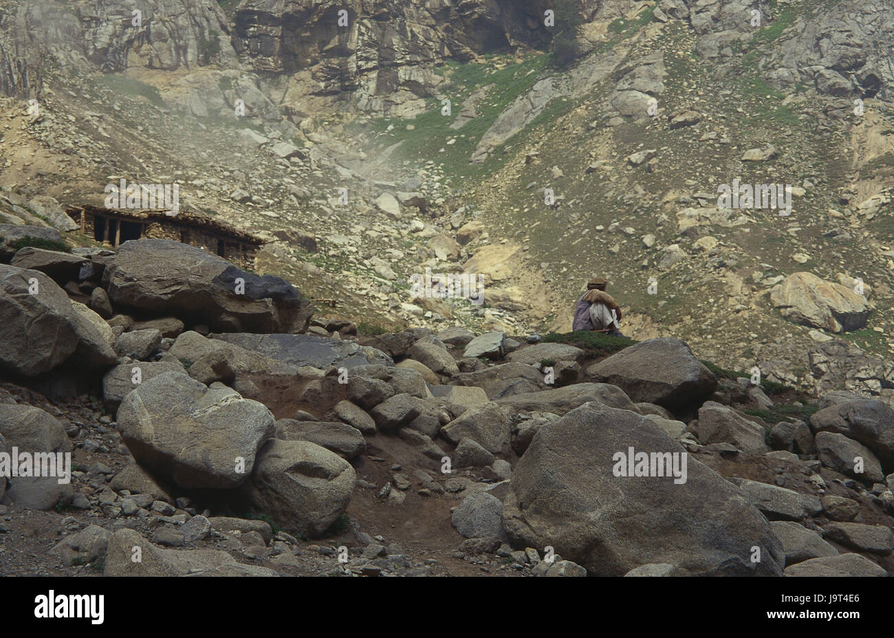 Pakistan,Chitral,mountain landscape,rock,man,sit,no model release,Asia,mountains,mountains,bile scenery,rocky,stony,local,people,only,loneliness,scanty,hopelessly,outside, - Stock Image