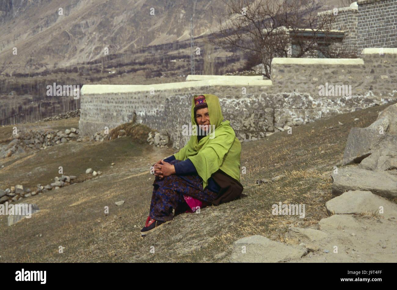 Pakistan,Karimabad,woman,Hunzukuc strain,sit,at the side,no model release,Asia,Karakorumgebirge,Karakorum,Hunzatal,Hunzukuc,tribe,locals,clothes,headgear,traditionally,outside,whole - Stock Image