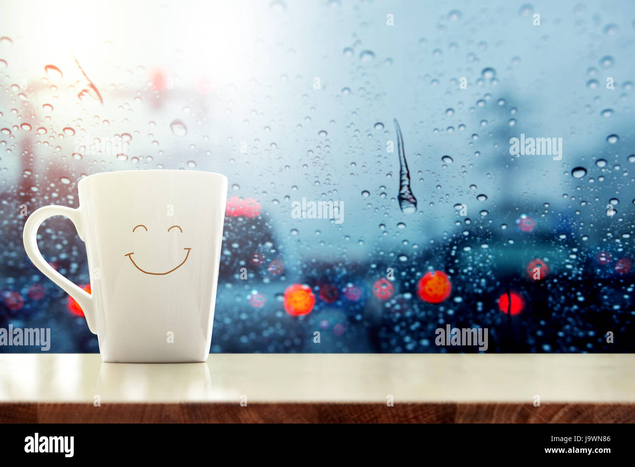 Happy Coffee Mug with smilely face on desk inside glass window, Blurred traffic jam light in city as outside view, - Stock Image