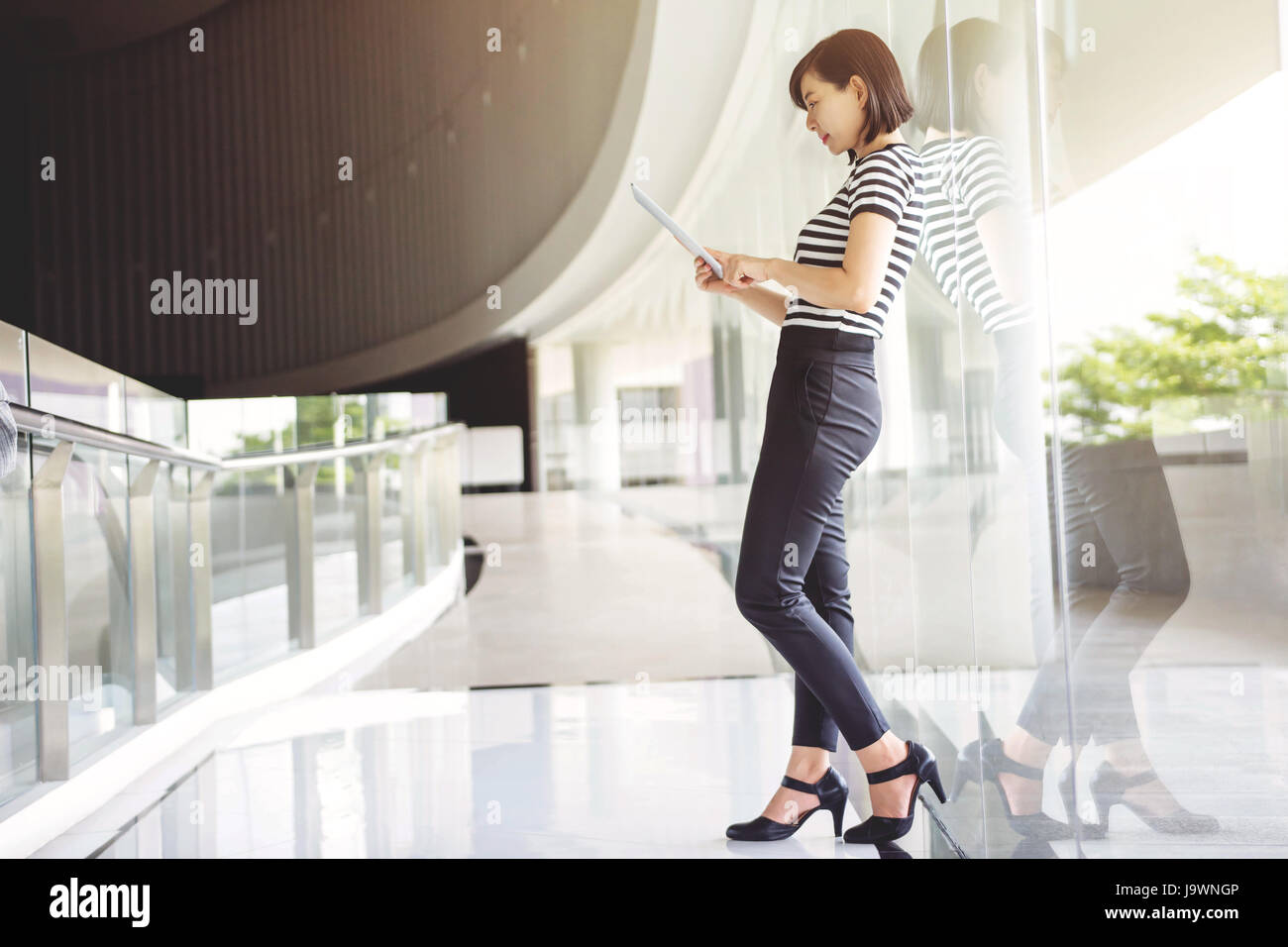 Business working woman reading data in digital tablet inside building, Social communicate technology in business - Stock Image