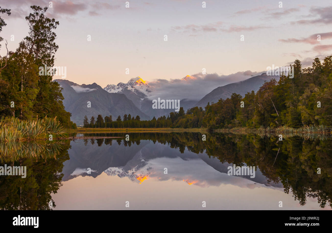Sunset, Mirror Island, Mt. Tasman and Mt. Cook, Reflection in Lake Matheson, Mount Cook National Park, Westland - Stock Image