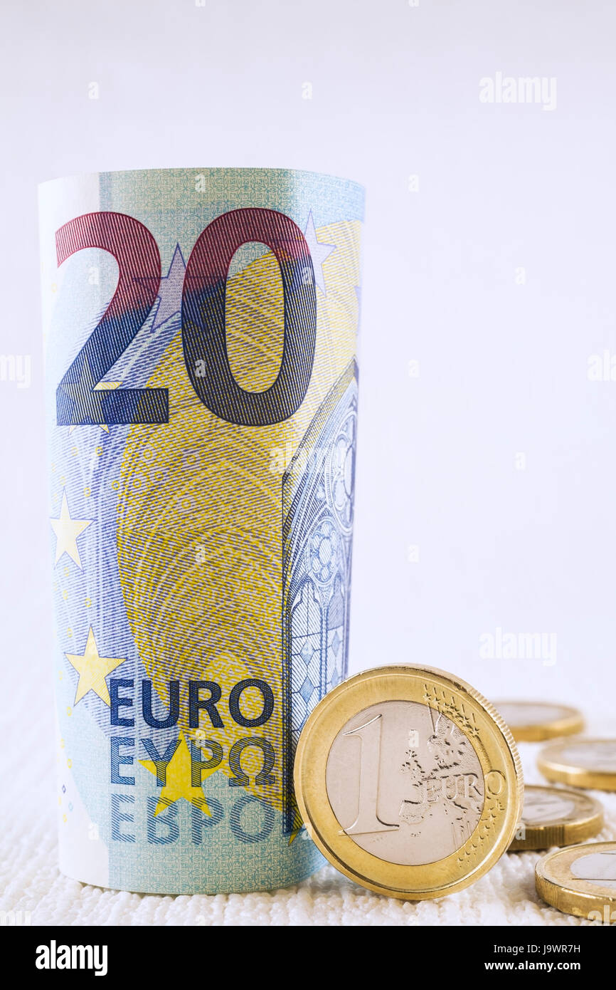 Rolled upright twenty Euros bank note with one Euro coin - Stock Image